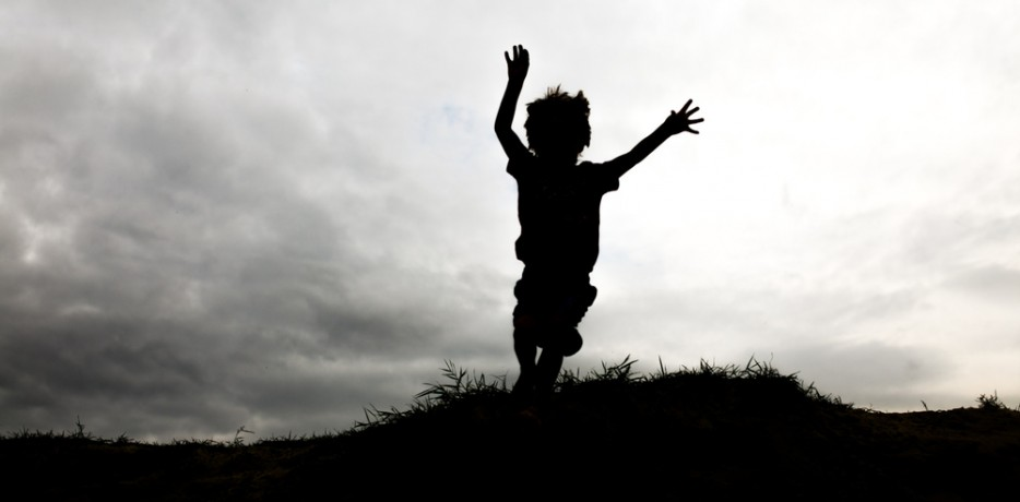 Boy jumping from a cliff
